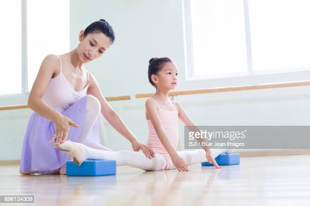young ballet instructor teaching girl in ballet studio - girl with legs spread stock photos and pictures