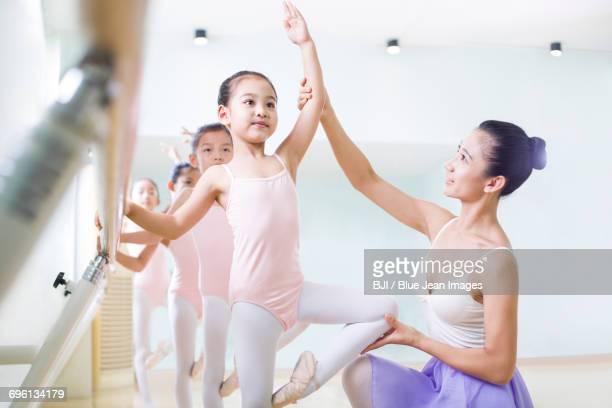young ballet instructor teaching girls in ballet studio - ballettstudio stock-fotos und bilder