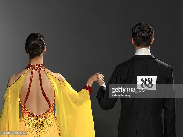 Young ballroom dancing couple holding hands, rear view
