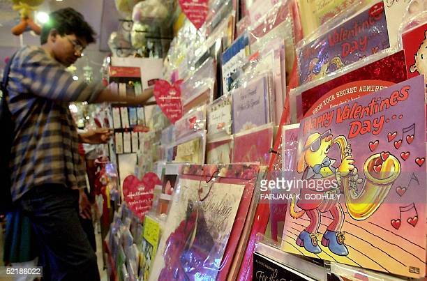 Young Bangladeshi man chooses a Valentine's Day card from a selection on display in a gift shop in Dhaka, 12 February 2005. A large number of...