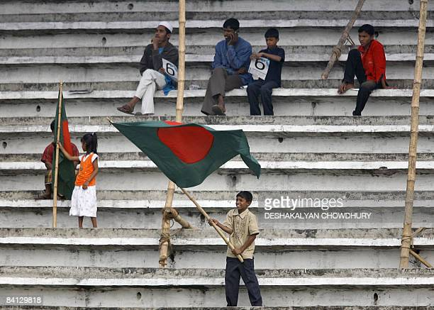 A young Bangladeshi supporter waves his country's national flag among mostlyempty stadium seating during the third day's play of the first Test match...