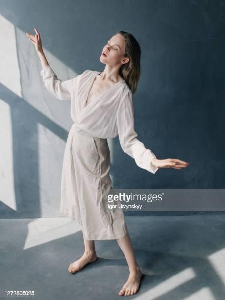 young barefoot woman standing hands raised - schauspielerin stock-fotos und bilder