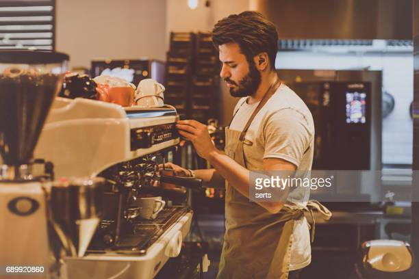 Young barista is making a coffee in cafe shop