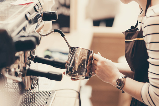 Young barista is making a coffee 523776406