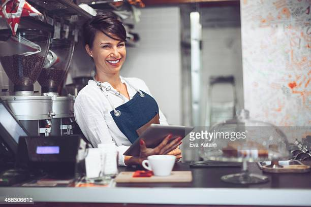 Young barista is using a digital tablet