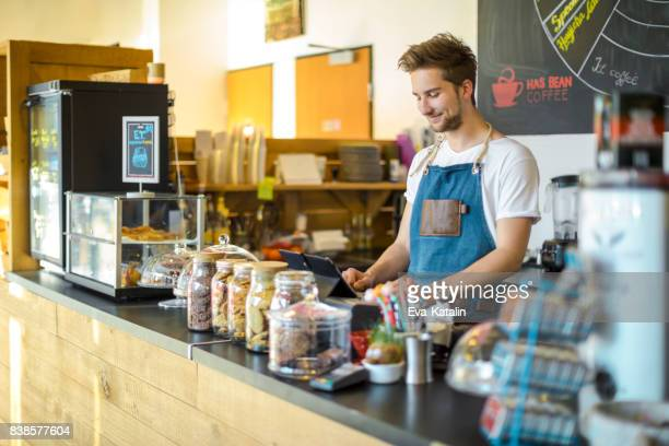 Young barista is working in a café