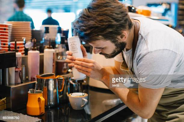 Young Barista Pouring Latte Art with Chocolate Sauce