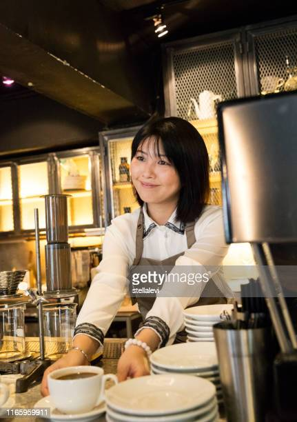 young barista serving customers at a cafe - stellalevi stock pictures, royalty-free photos & images