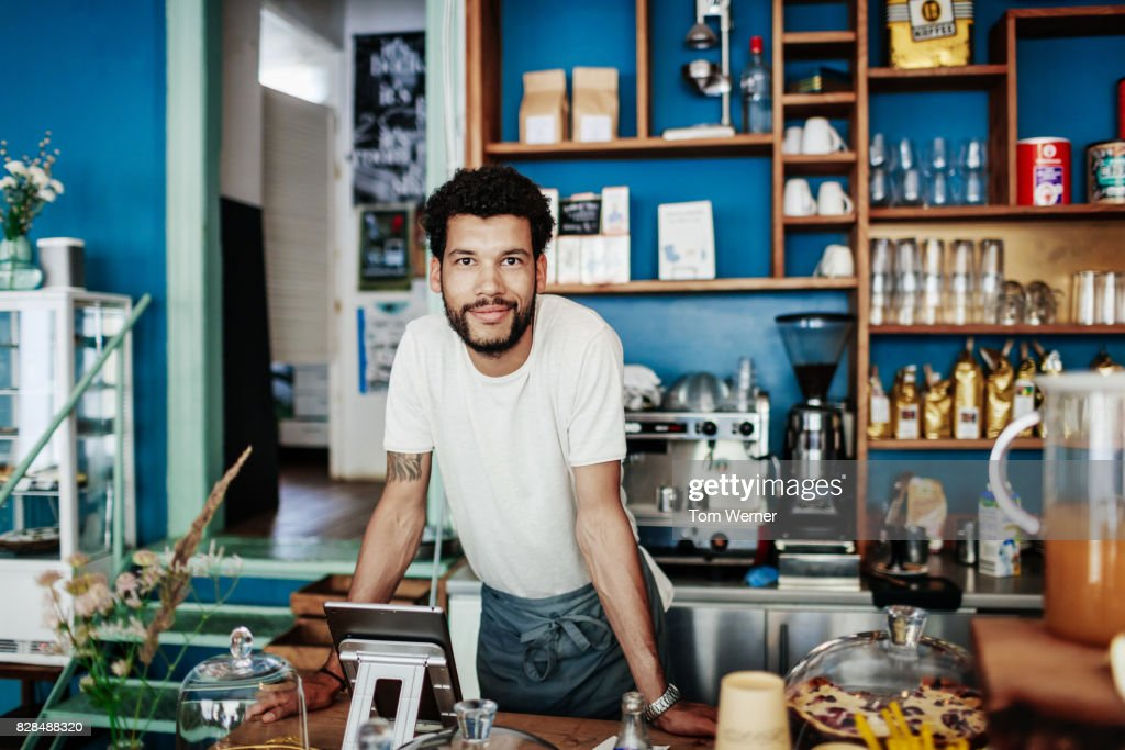 Young Barista Smiling Leaning On Coffee Shop Counter : Stock Photo