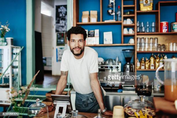 young barista smiling leaning on coffee shop counter - affaires finance et industrie photos et images de collection