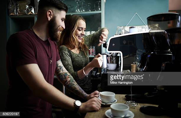 Young baristas preparing drinks in cafe