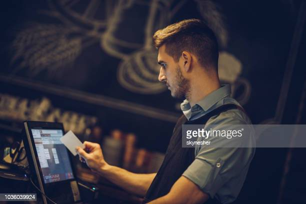 young bartender at the point of sale in a pub. - cash register stock pictures, royalty-free photos & images