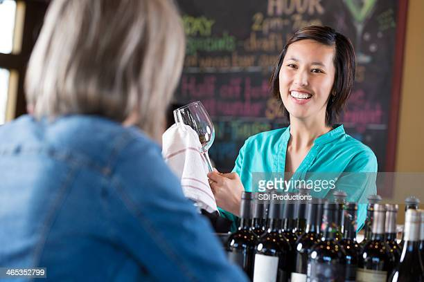 Young bartender conversing with customer while working