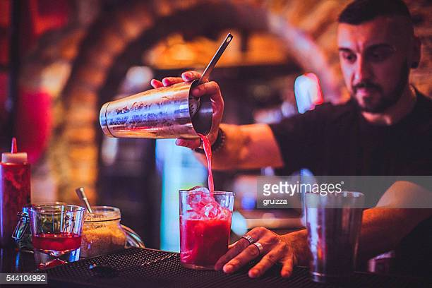 Young bartender pouring cocktail in a nightlife bar