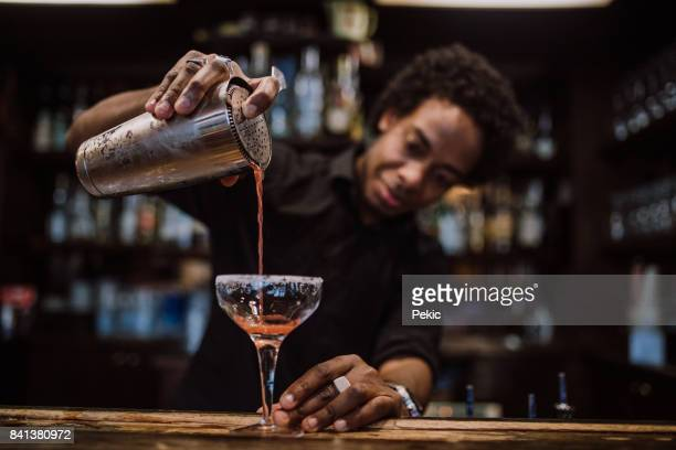 young bartender pouring cocktails in a cocktail bar - preparation stock pictures, royalty-free photos & images
