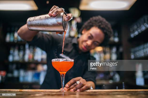 young bartender pouring cocktails in a cocktail bar - mixing stock pictures, royalty-free photos & images