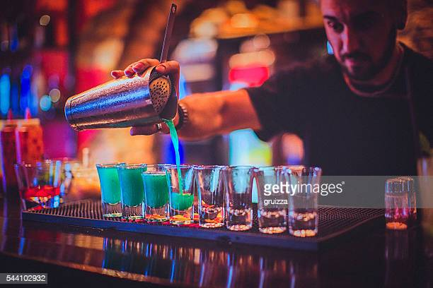 Young bartender pouring cocktails in a nightlife bar