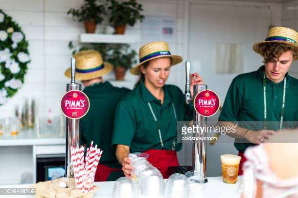 young bartenders serving pimm's on tap at pop-up bar, london, uk - serving sport stock photos and pictures