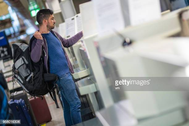 Young bascpacker checking in at an airport counter
