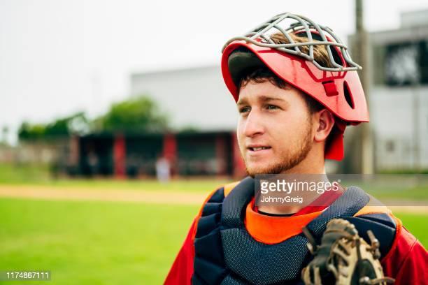 マスクと胸のプロテクターを着用した若い野球キャッチャー - 高校野球 ストックフォトと画像