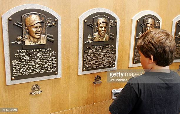 A young baseball fan looks at plaques of players inducted into the National Baseball Hall of Fame and Museum during the Baseball Hall of Fame weekend...