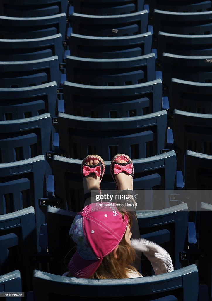 A young baseball fan rests her feet on top of empty bleachers after the New York Yankees defeated the Boston Red Sox 8-1 during a spring training game at George M. Steinbrenner Field in Tampa, Fla., March 18, 2014.