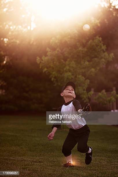 young baseball player about to catch baseball