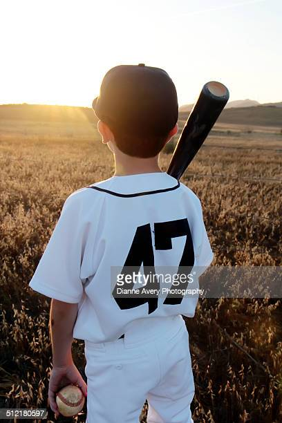 Young baseball player from behind sunset