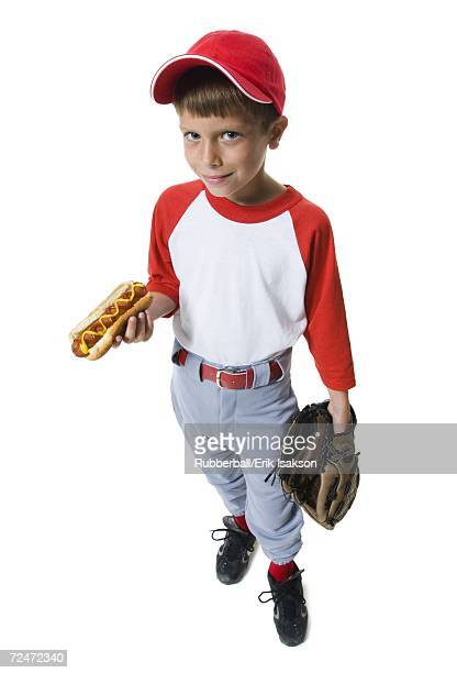 Young baseball player holding a hot dog