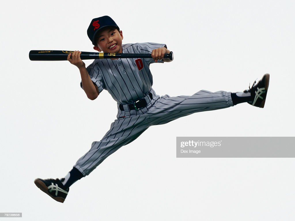 Young Baseball player holding bat in mid-air : Stock Photo