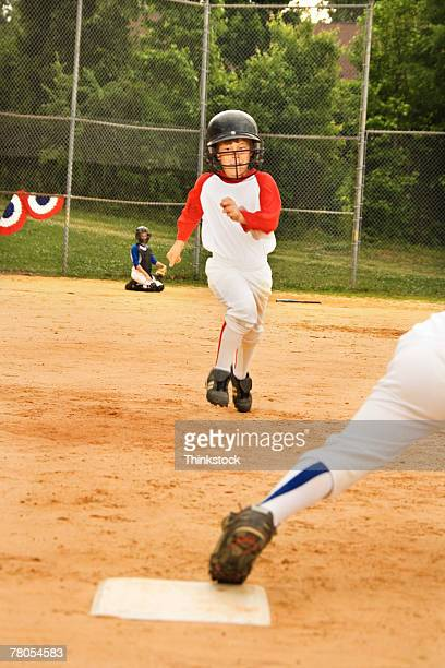 young baseball player running toward first base - human body part stock pictures, royalty-free photos & images