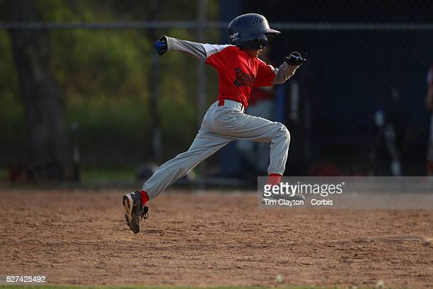 A young baseball player runs hard as he attempts to steal second base during the Norwalk Little League baseball competition at Broad River Fields...