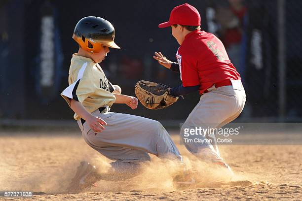 A young baseball player slides into second base during the Norwalk Little League baseball competition at Broad River Fields Norwalk Connecticut USA...