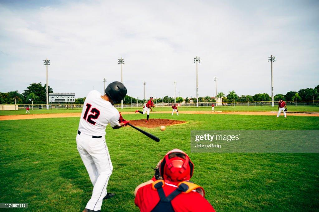 Young baseball player swinging his bat at thrown pitch : Stock Photo