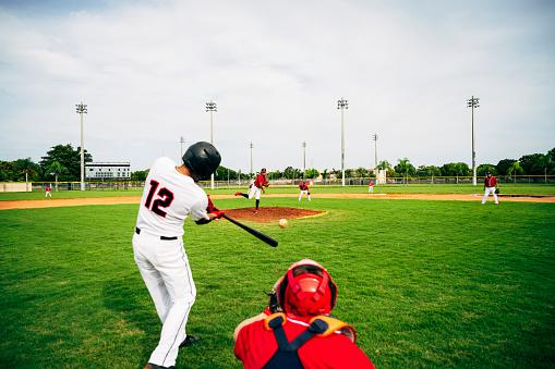Young baseball player swinging his bat at thrown pitch 1174867113