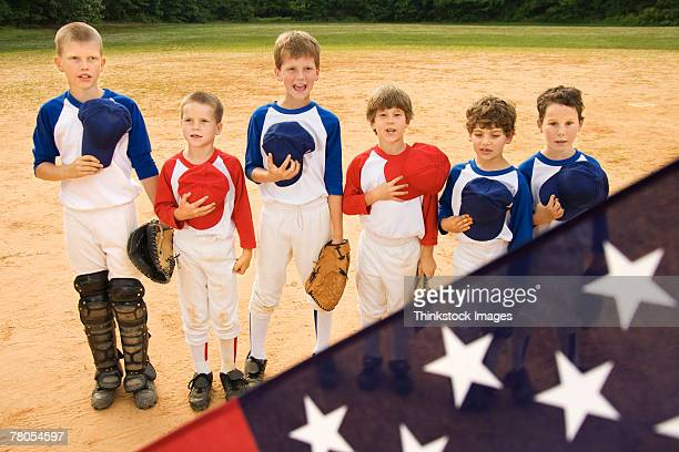 Young baseball players holding caps in front of American flag