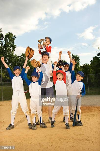 Young baseball team and coach celebrating their victory with trophy