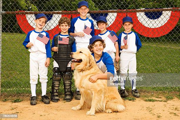 Young baseball team holding American flags while posing with dog