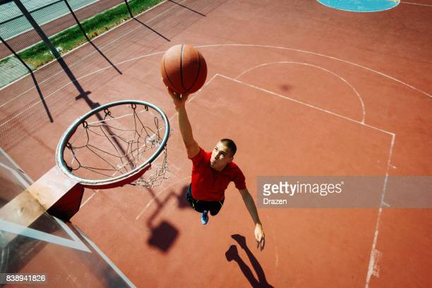 Young basketball player in slam dunk position