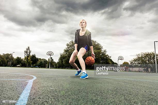 Young basketball player training at playground in London