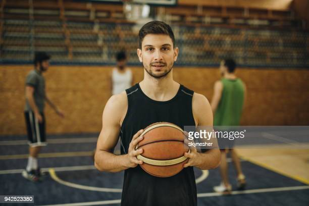 young basketball player with a ball on playing field. - giocatore di basket foto e immagini stock
