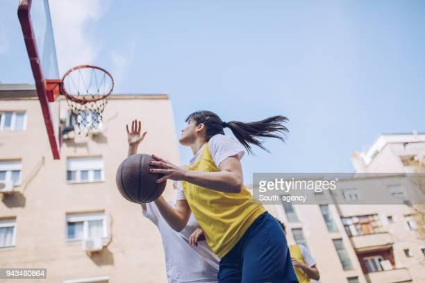 Junge Basketballer spielen Basketball auf dem Platz