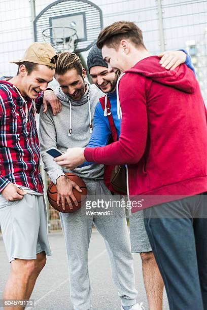 Young basketball players with smartphone laughing