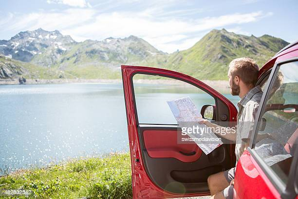 Young beard man on road trip consulting map for directions