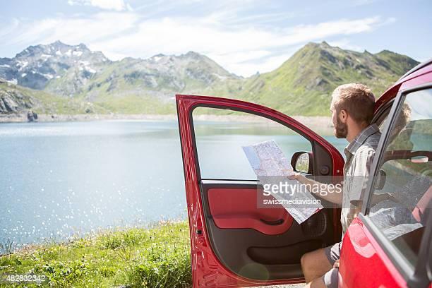 Junger Mann mit Bart auf road trip consulting Karte für die Anfahrt