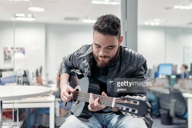 young bearded brazilian man playing guitar in office in Rio