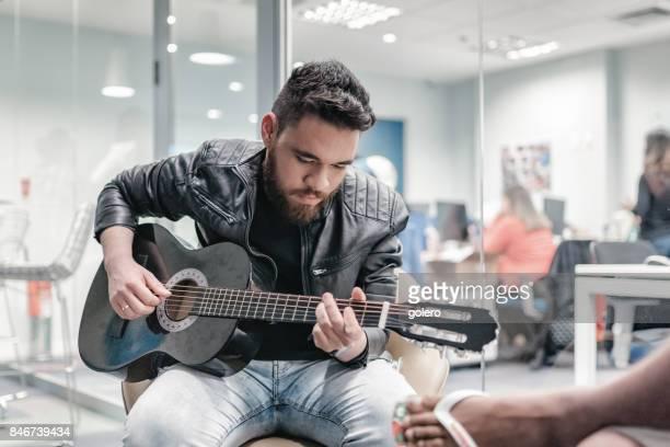young bearded brazilian man  playing guitar in office