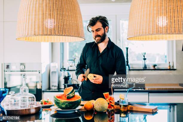Young bearded man enjoying watermelon and making salad in the kitchen