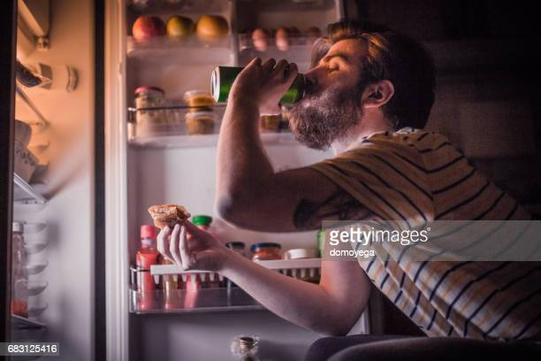 Young bearded man having a beer and late night snack in front of the refrigerator