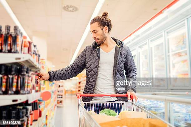 young bearded man in a supermarket. - man bun stock pictures, royalty-free photos & images